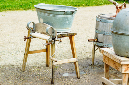 devise: Old fashioned mangle with washing tub on top and crank at side. Several old laundry utensils partly visible to the right. Ground is wet gravel with small puddle under mangle. No person visible.