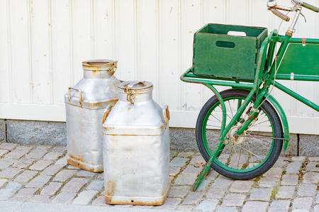 merchandize: Green vintage bicycle with luggage crate in front to hold merchandize and goods. Two metal milk bottles on the ground in front of it. This has a real retro feel to it. Street is made of granite stone. Stock Photo