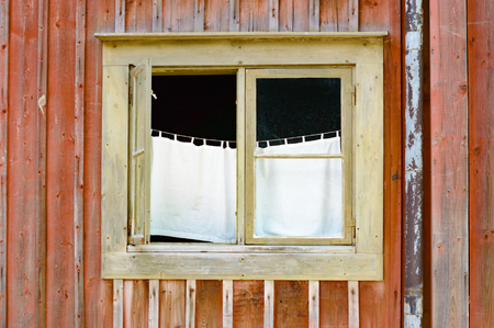 tearing down: Open window on an old red wooden house. Inside hangs a white very simple curtain from a rope or string. Drainpipe visible beside window. No person in picture. Place has a weathered and run down look.