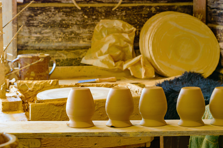 recourse: A row of unfired clay pots at a workstation in a pottery workshop. Clay is still soft and will be worked on some more before firing. Clay covered workstation blurred in background. Stock Photo