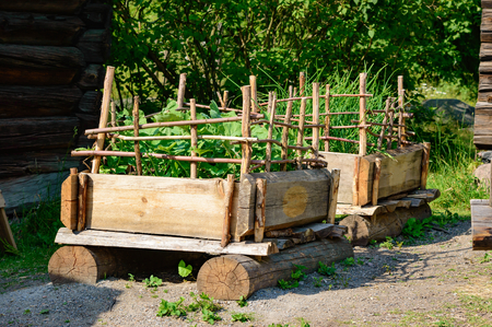 animals feeding: Pallet gardening in the old days with timber and plank to form a pallet of sort. Vegetables are grown in soil inside the pallet and sticks of wood form protection against animals feeding on crop.