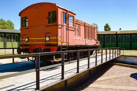 diesel train: A red diesel train standing on a rotating switch. The switch is used to maneuver the trains so they can be driven in through the correct door on the service building in the background.