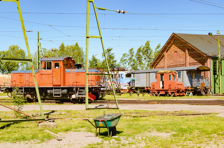 inoperative: Abandoned and working trains and cars outside a train service depot. Wheelbarrow in foreground and electric cables in the sky. Part of service building to the right.