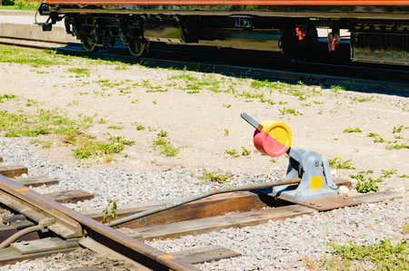 transpozycji: Red and yellow laver to switch tracks for incoming or outgoing trains. Lower part of a railroad car in background.