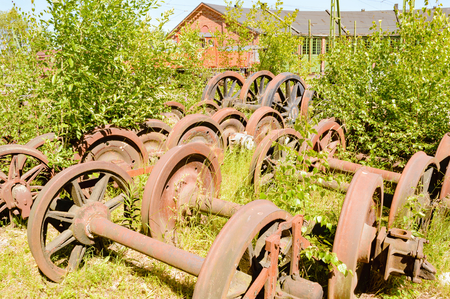 stockpile: A stockpile of old, rusty and abandoned train wheels lying in the grass close to train service depot.