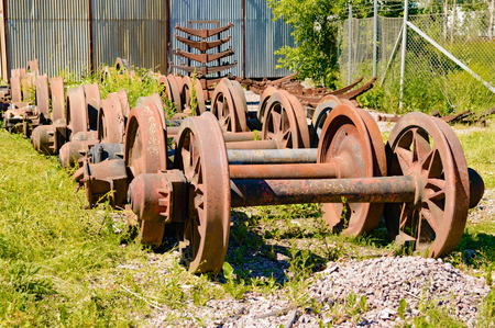 iron hoops: A stockpile of old, rusty and abandoned train wheels lying in the grass close to train service depot.