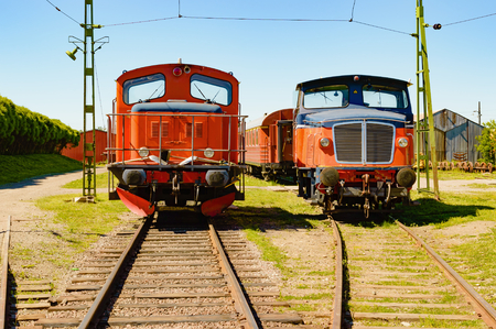 side order: Two red diesel locomotives side by side on railroad tracks. These are in working order and are waiting for a new mission on the station area. Stock Photo