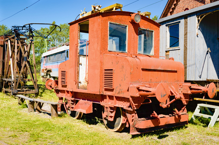 jilted: Small orange abandoned train wreck with some rust. Train car and other junk in background. Door is missing and no person is visible. Green grass on ground. Stock Photo