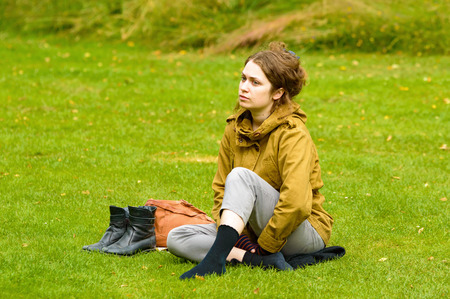 tantalizing: Smaland, Sweden - July 24, 2015: Unknowns young adult female sitting relaxed in the grass with her shoes off, looking a bit dreamy with eyes focused far into the distance.