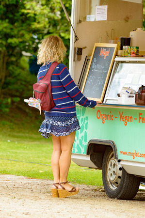 tantalizing: Smaland, Sweden - July 24, 2015: Attractive unknown woman stand in front of fast food wagon to purchase some food. She is wearing a short skirt, a sweater and heels, back towards you.