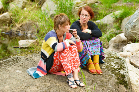 tantalizing: Smaland, Sweden - July 24, 2015: Two young adult females sitting on granite rock near a small creek having a talk. They are dressed in coloful garments. One drink something.