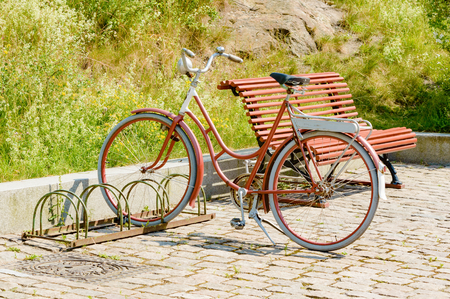 timeless: A red vintage bicycle standing parked in a bike stand close to wooden bench. Street is made of blocks of granite.
