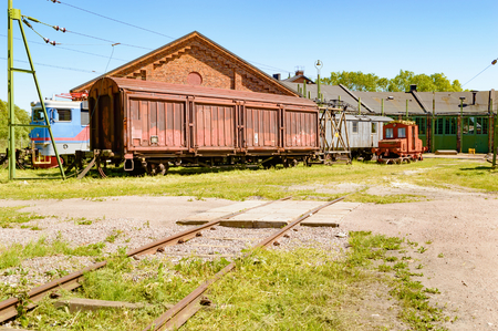 tarnished: Abandoned trains and cars outside an old service depot with railroad tracks leading up to building. Small railway crossing in foreground. No person visible. Stock Photo