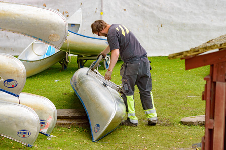 aluminum wheels: Smaland, Sweden - July 24, 2015: Nature tourism is booming in Sweden. Here is an unknown worker at a canoe rental place attaching transport wheels to one of the aluminum canoes.