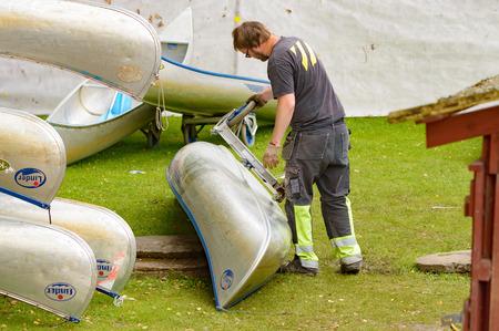 workingman: Sm�land, Suecia - 24 de julio de 2015: el turismo Naturaleza est� en auge en Suecia. He aqu� un trabajador desconocido en un lugar alquiler de canoas adjuntando ruedas de transporte a una de las canoas de aluminio.