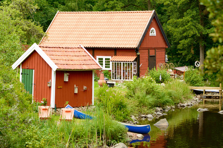 idealized: Smaland, Sweden - July 24, 2015: Living close to water gives higher taxes in Sweden. Here is a small red wooden house near a still river. Blue canoe rest by the shore.