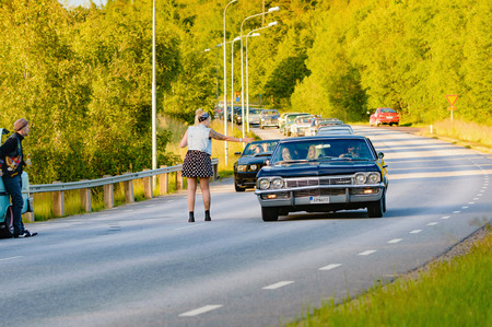 Ronneby, Sweden - June 26, 2015: Car break down and cause some chaos on the street during a road cruise for veteran cars. Drunk passengers behave unsafe and venture into street.