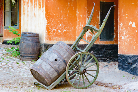 open hole: Cart with a wooden cask or barrel outside a building. Another cask stands in the background. Walls on building are orange. Place has a vintage feel to it. Open hole in cask.
