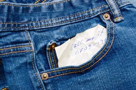 secret: Secretive handwritten message in denim pocket, from someone that wants a call about something. Perhaps the note was found before laundry and suggests a secret lover. Note is wrinkled and ink is blue. Stock Photo