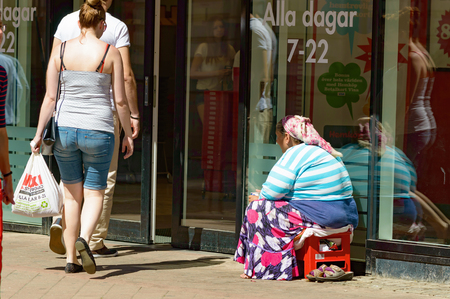 beggary: Karlskrona, Sweden - August 03, 2015: Unknown female beggar sitting outside a store with people walking by. Beggary is a growing problem in many Swedish cities. Editorial