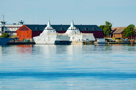 stealth: Karlskrona, Sweden - August 03, 2015: Two Visby class Swedish navy stealth corvettes moored at the naval base harbor as seen from the water looking in.