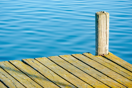 gnarled: Detail of an old, unpainted wooden pier with calm and still water in background. Jetty is empty and the wood is weathered and gnarled. Poles are cracked. Copyspace in water.