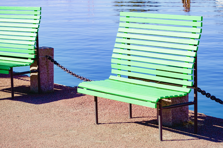 water stone: Empty green wooden bench close to water. Stone pillar with chain behind bench. Still, calm water in background.