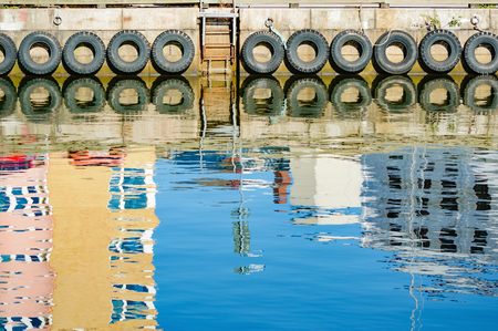 car lots: Reflections in the water at a harbor. Lots of rubber car tires hang along pier and are reflected in the water. Reflections of houses are visible too. Copyspace in water. Stock Photo