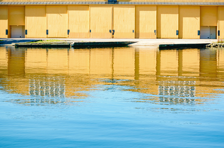 housing lot: Yellow doors on a hangar are reflected in the calm water in front.
