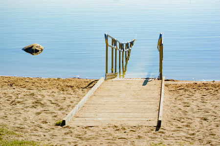 make public: A wheelchair ramp into the sea water to be used by people with disabilitiy or handicap. A very simple and easy way to make public bathing accessible to all. Calm summer day and sandy beach. Stock Photo