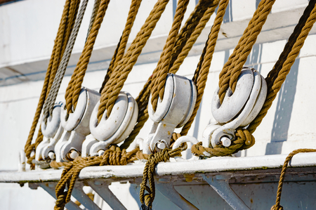 twined: Nautical tool for distributing the load of heavy sails ans such. Block and tacle or pulleys on the outside of a sailing ship.