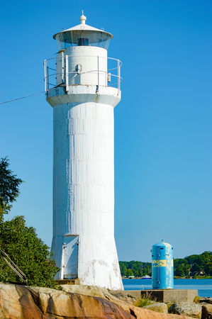 navigational light: A white, small lighthouse against clear blue sky in summer. Some water visible and rocks in the foreground. Stock Photo