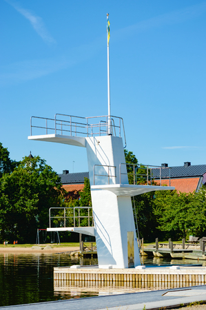 no person: A white diving board or tower against a clear blue sky. Reflections are seen underneath. No person visible. Stock Photo