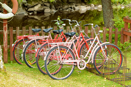 rented: Smaland, Sweden - July 24, 2015: Renting a bike to move around with is a growing business in Sweden. Here are some bikes ready to be rented. Calm river in background. Editorial