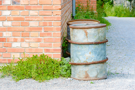 unmarked: Two metal oil barrels standing in the corner of an old brick industrial building or factory.