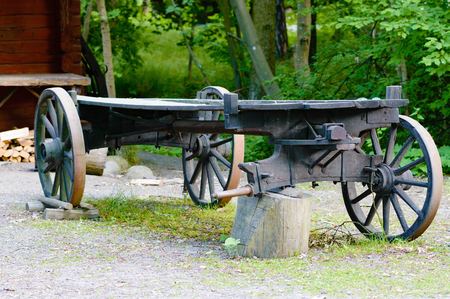 be missing: A black undercarriage of a wagon is missing a wheel and is standing on a wooden stump for support. Wheel will be replaced. Stock Photo