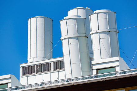 freshening: Air vents on top of an industrial building. Some of the vents are slightly tilted. White metal against a clear blue sky.