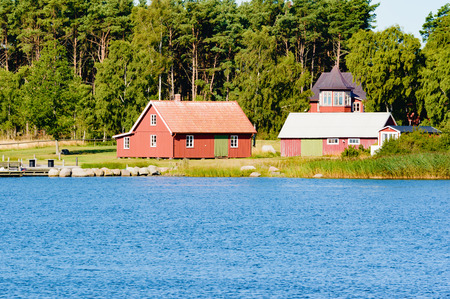 home prices: Kristianopel, Sweden - August 13, 2015: Typical coastal private home in the Swedish archipelago as seen from the sea. Coastal living is very popular and housing prices are on the rise.