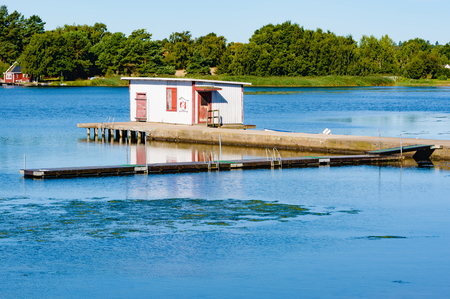 hardly: A small bathing hut or cabin on the end of a concrete bridge. Calm warm water invite to a swim. Surrounding is lovely with some forest in the background. Weather is sunshine and hardly any wind.