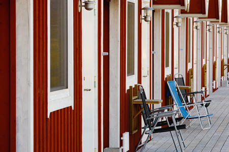 wall mounted: A row of tourist apartments close together. Some outdoor furniture visible outside one apartment. All doors closed. Small collapsible wall mounted tables at each apartment.