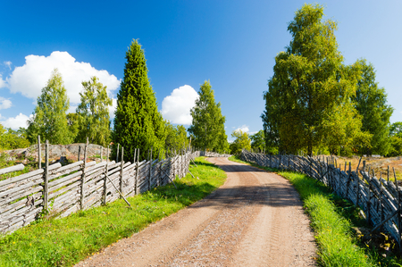 open country: Old country road with old fashioned wooden fencing at roadside. Road moves through very fine landscape that is conserved and kept open. Fine summer day with sunshine. Smaland, Sweden. Stock Photo