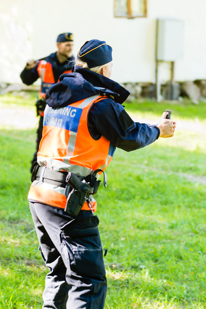 education in sweden: Vaxjo, Sweden - September 09, 2015: Police education. Outdoor weapons and apprehension training in public area. Female trainee with pepper spray in hand. Partner ready to assist.