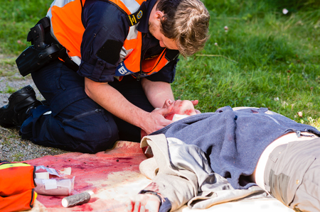 the unconscious: Vaxjo, Sweden - September 09, 2015: Police education. Outdoor medical training in public area. Police hold bleeding neck on pretending victim. Blood stains on blanket. Victim unconscious.