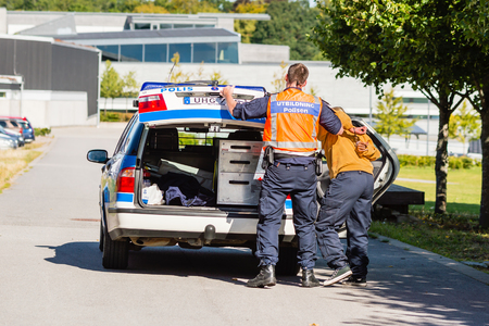 apprehension: Vaxjo, Sweden - September 09, 2015: Police education. Outdoor weapons and apprehension training in public area. Police hold arrested pretending criminal while opening car trunk. Criminal in cuffs. Editorial