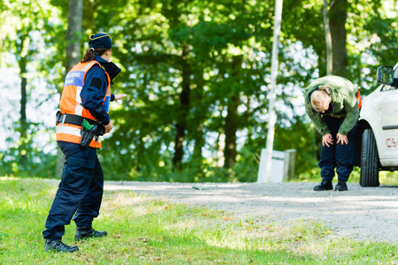 education in sweden: Vaxjo, Sweden - September 09, 2015: Police education. Outdoor weapons and apprehension training in public area. Pretending criminal has just been sprayed by pepper spray and bend down hurting.