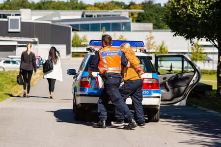 education in sweden: Vaxjo, Sweden - September 09, 2015: Police education. Outdoor weapons and apprehension training in public area. Police walk arrested pretending criminal from car. Civilians pass by.