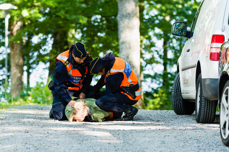 Vaxjo, Sweden - September 09, 2015: Police education. Outdoor weapons and apprehension training in public area. Two female trainees take down and cuff female pretending criminal.