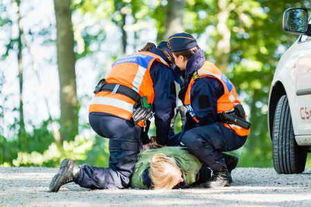 trainees: Vaxjo, Sweden - September 09, 2015: Police education. Outdoor weapons and apprehension training in public area. Two female trainees take down and cuff female pretending criminal.