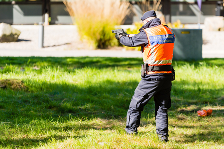 education in sweden: Vaxjo, Sweden - September 09, 2015: Police education. Outdoor weapons and apprehension training in public area. Male trainee point a gun at criminal outside picture. Copy space.