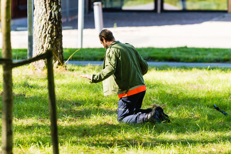 education in sweden: Vaxjo, Sweden - September 09, 2015: Police education. Outdoor weapons and apprehension training in public area. Male trainee pretending criminal on his knees in the grass.